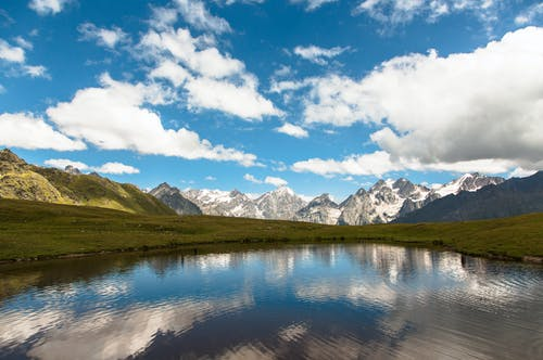 Snowy and green mountains against pond under cloudy blue sky
