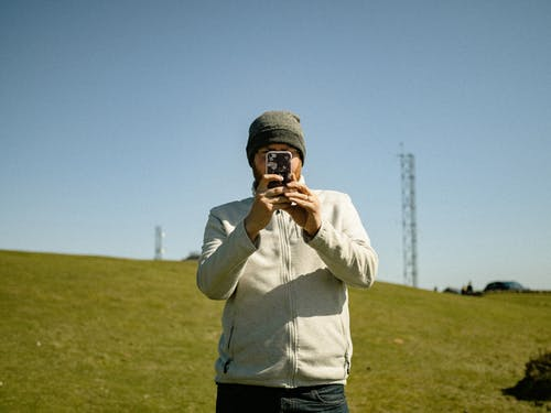 Concentrated male in hat taking picture on mobile phone while standing on lush grassy meadow and looking at camera
