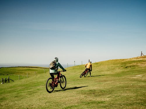 Two Bikers Riding a Bike on a Grassy Field