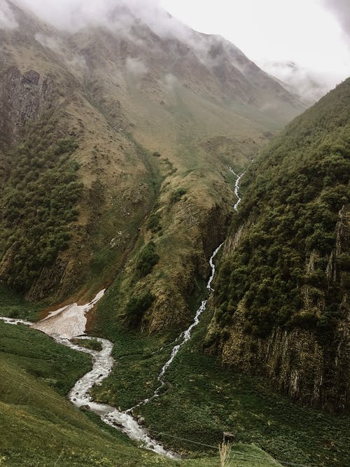 Picturesque view of cascades and wavy river with foam on mount with moss in misty weather