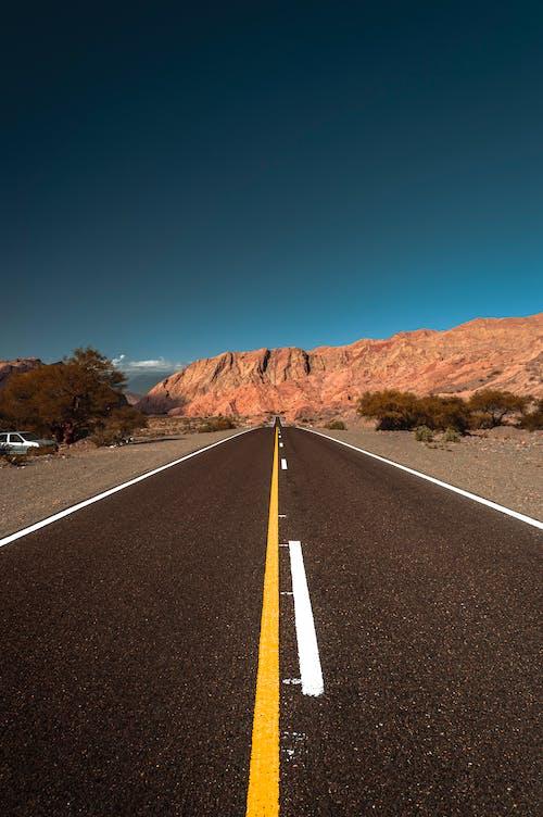 Black Asphalt Road Between Brown Mountains
