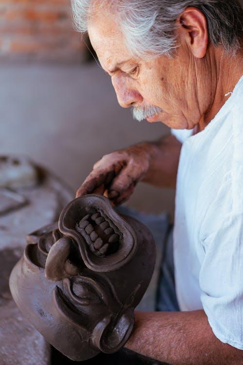 An Elderly Man Making a Mask