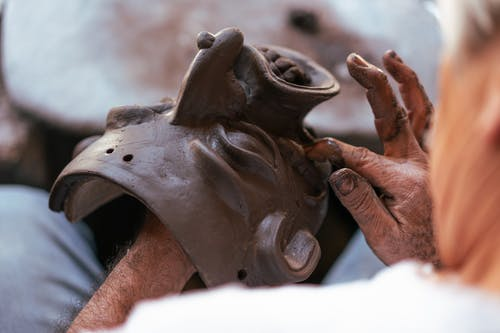 A Person Making a Creepy Mask Made of  Clay