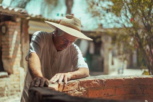 An Elderly Man Standing Beside a Brick Pit