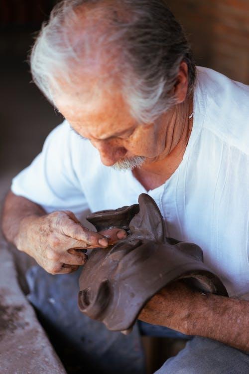 An Elderly Man Making a Clay Mask