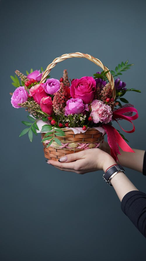 Crop unrecognizable female demonstrating wicker basket full of fresh colorful roses and green leaves on gray background in light room