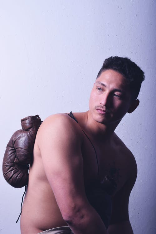 Boxer with glove on back on light background