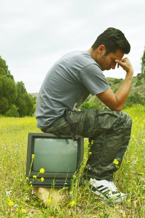 Side view of thoughtful male touching forehead while sitting on vintage television on meadow in countryside