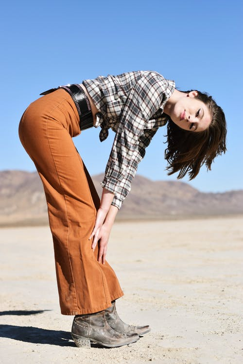 Side view of stylish young woman in checkered shirt and pants touching legs while looking at camera under blue sky