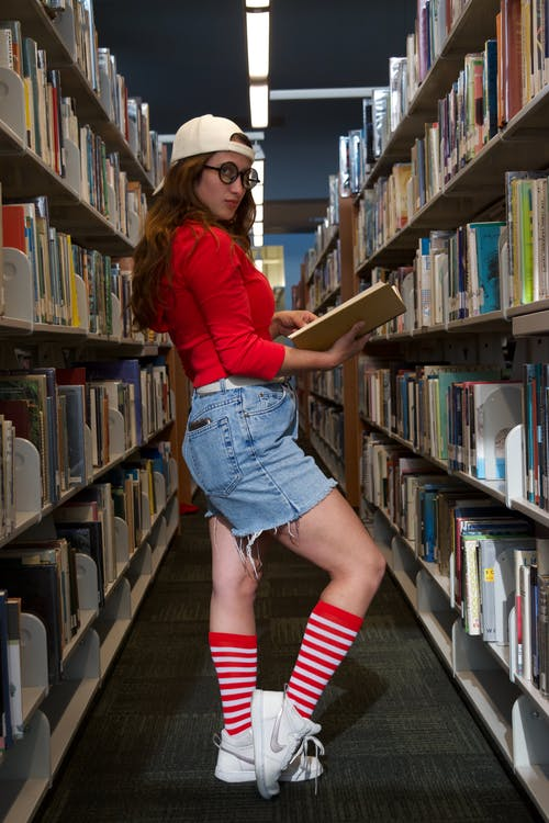 Side view of young female in knee socks with striped ornament standing with textbook in library while looking at camera