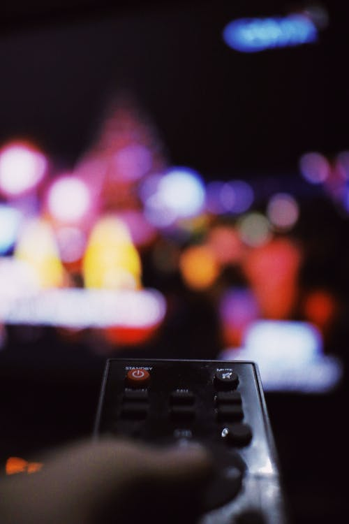 Soft focus of person with TV remote switching channels while watching movie in living room at home during free time