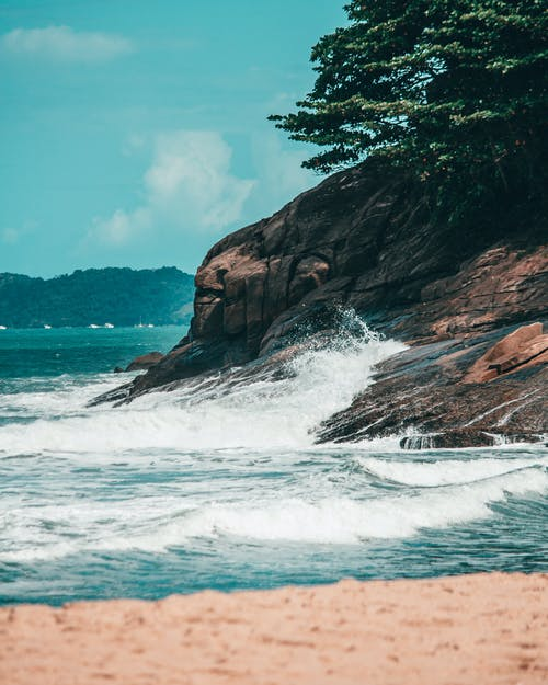 Scenery view of sea waves splashing on stony shore and sandy beach in tropical resort