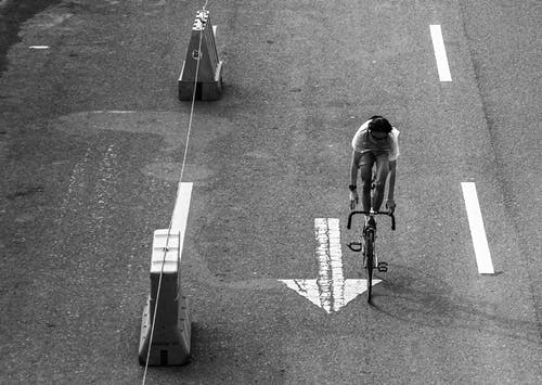 Monochrome Photo of a Person Riding a Bicycle on an Asphalt Road