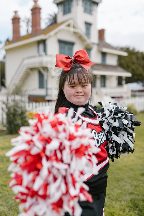 A Woman in Cheerleader Outfit Holding Pompoms