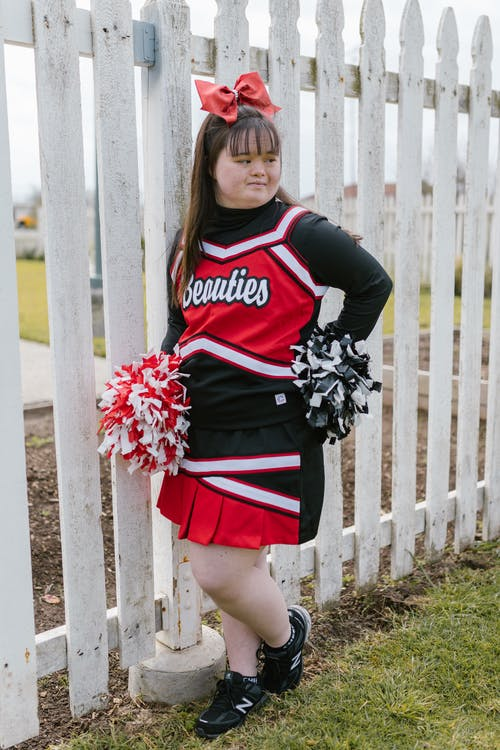Woman in Cheerleader Outfit Standing beside Wooden Fence