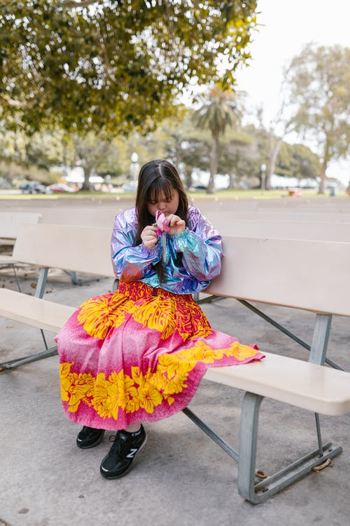 A Girl in Floral Dress Sitting on a Bench