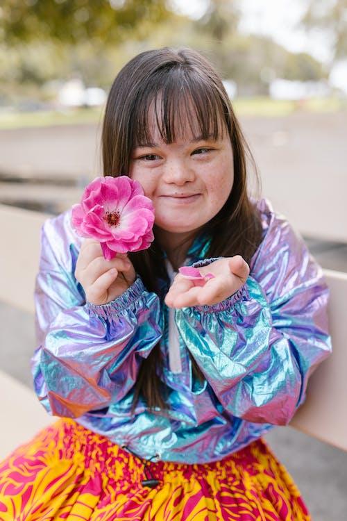 Menina De Vestido Azul E Rosa Segurando Uma Flor Rosa