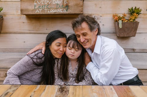 Parents Hugging Their Daughter