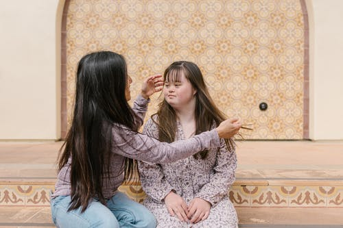 Mother Fixing Her Daughter's Hair