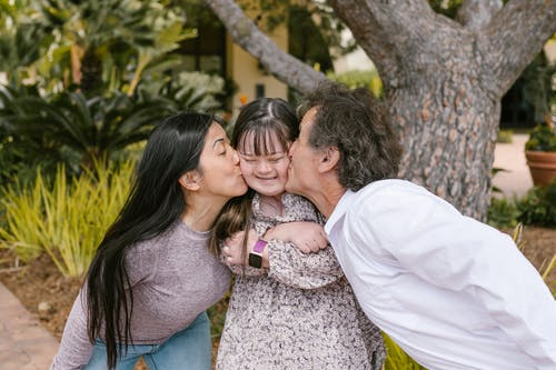 Parents Kissing Their Daughter's Cheeks
