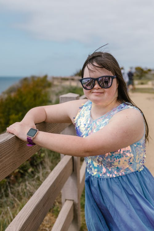 Woman in Blue Dress and Sunglasses Standing by the Wooden Fence