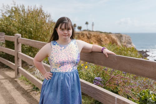 Girl in White and Pink Floral Dress Standing on Brown Wooden Fence