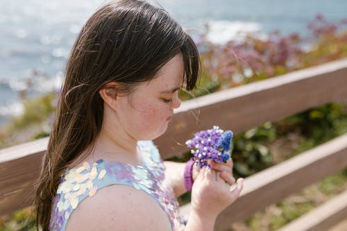 A Girl Holding Purple and Blue Flowers