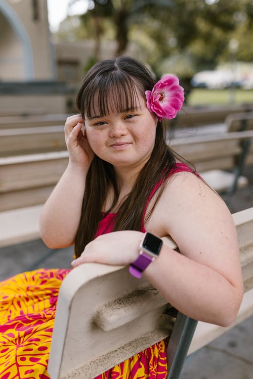 A Girl with a Flower on Her Ear Sitting on a Bench