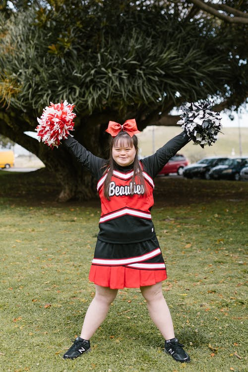 A Happy Woman in Cheerleader Outfit Holding Pompoms