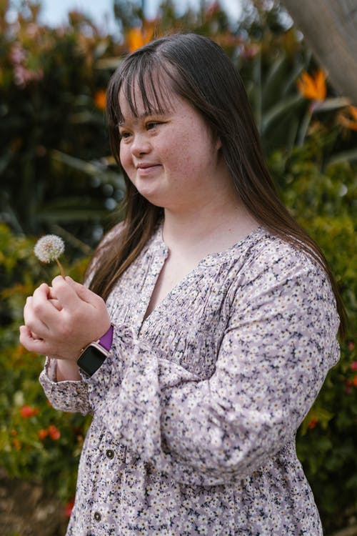 A Girl in a Floral Top Holding a Dandelion