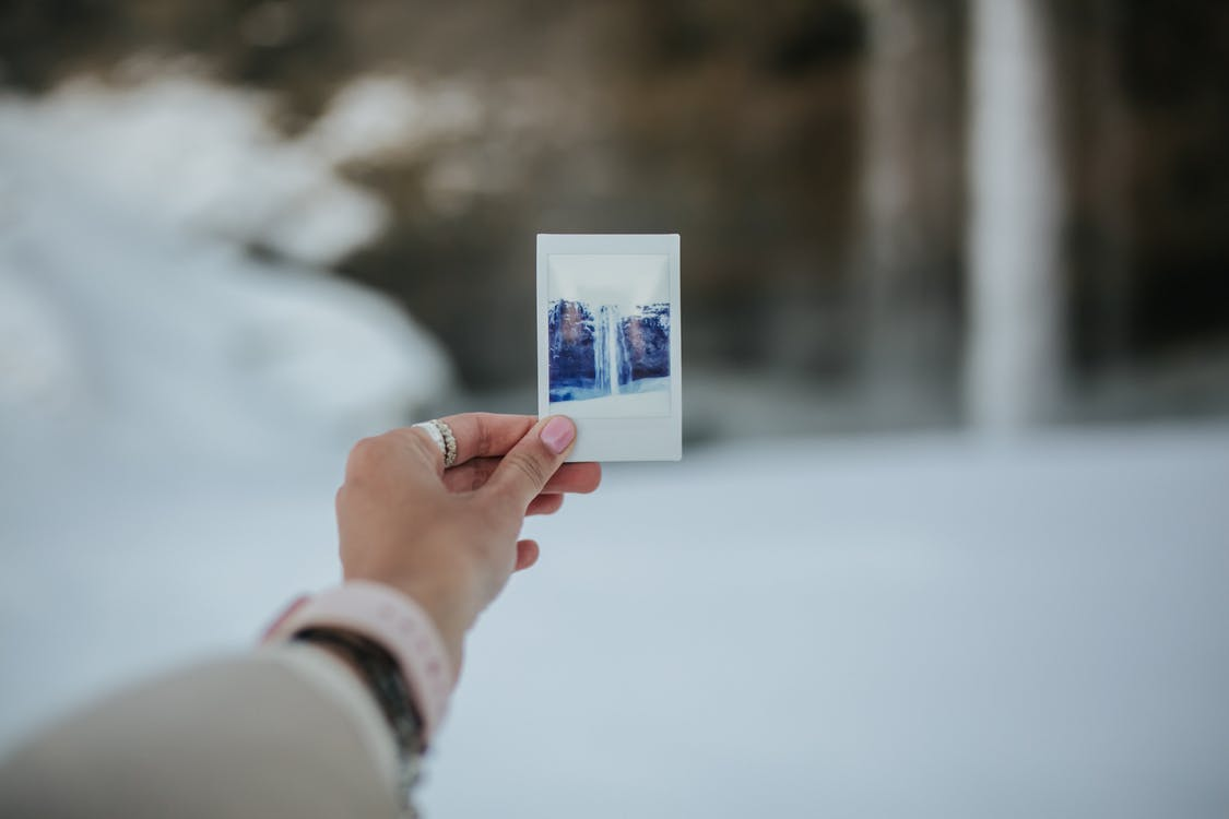 A Person Holding a Photo of Waterfall