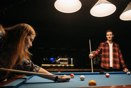 A Man and a Woman Playing Billiards