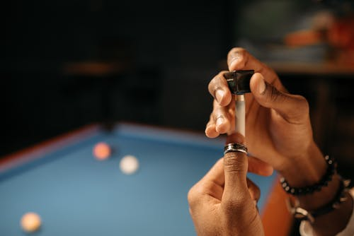 A Person Putting Chalk on a Cue Stick