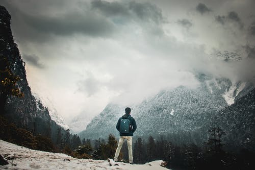 Full body back view of anonymous backpacker with rucksack contemplating mountain ridge while standing on edge of snowy mount in foggy weather