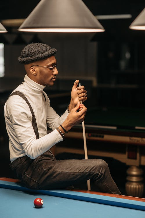 A Man Sitting on the Billiard Table while Holding a Cue Stick