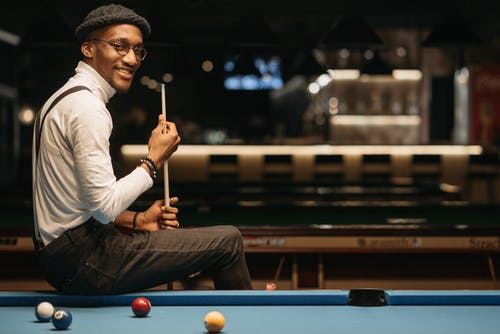A Smiling Man in White Turtle Neck Sleeves Holding a Cue Stick while Sitting on a Pool Table