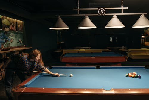 Woman Hitting the Ball with Cue Stick