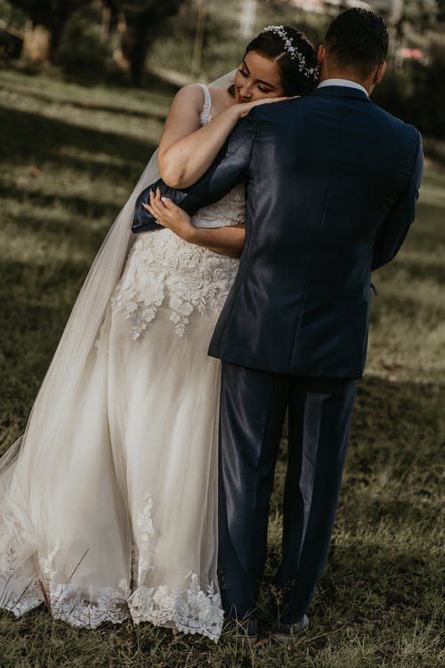 Ethnic bride in white dress leaning on shoulder of unrecognizable groom while embracing on meadow during festive occasion