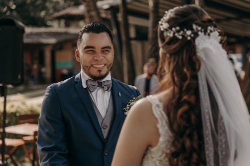 Man in Blue Suit Jacket Smiling Beside Woman in White Floral Lace Wedding Dress
