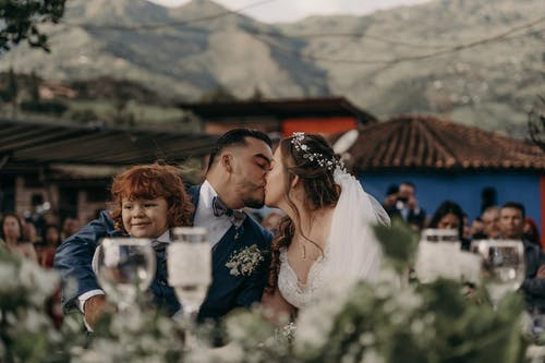 Man in Black Suit Jacket Kissing Woman in White Floral Dress
