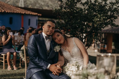 Man in Black Suit and Woman in White Wedding Dress Sitting on Brown Wooden Bench during