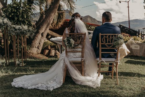 Bride and Groom Sitting on Brown Wooden Chair Under Green Tree