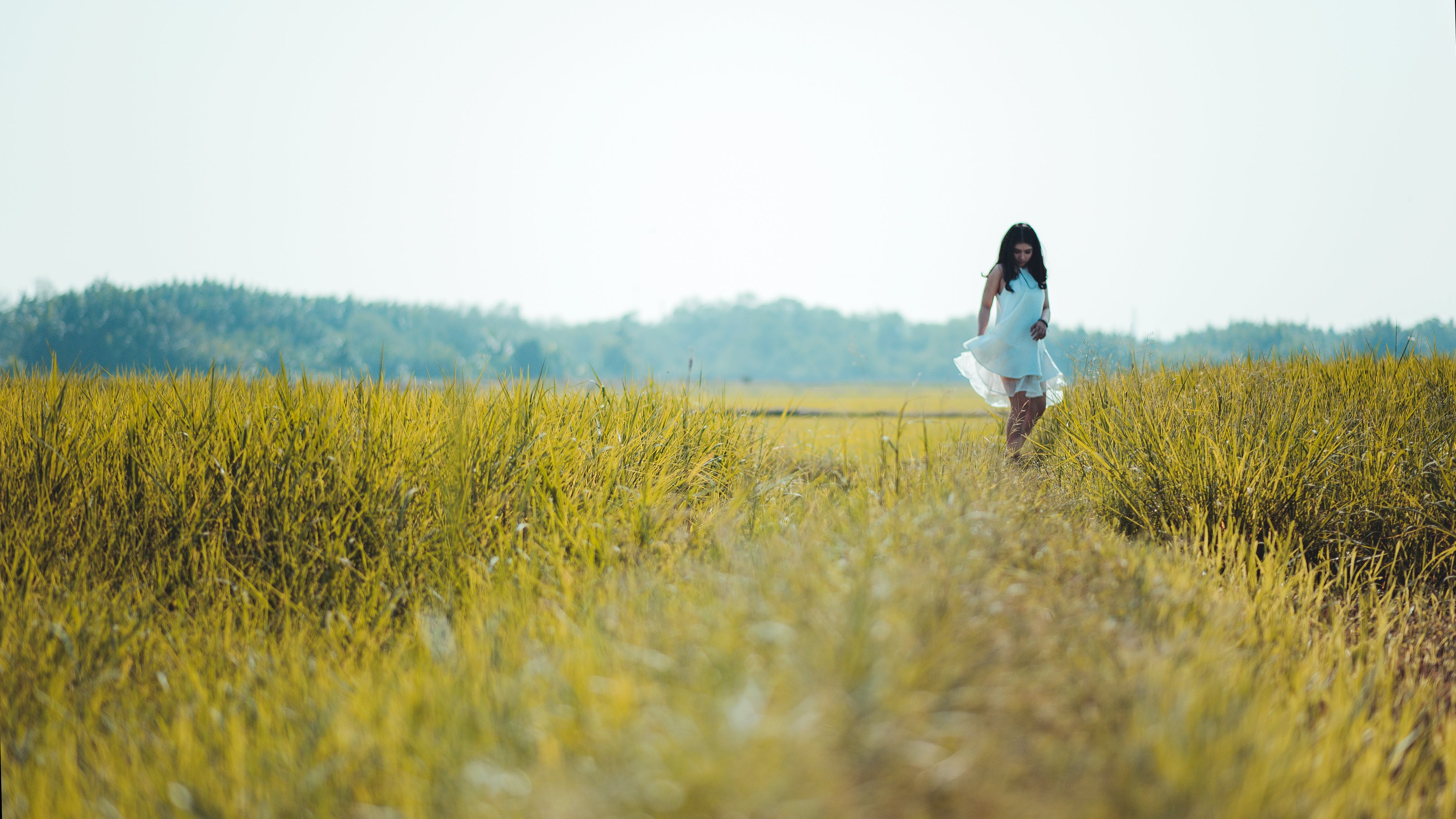 Depth of Field Photography of Woman Wearing White Sleeveless Dress Standing on Green Grass Field