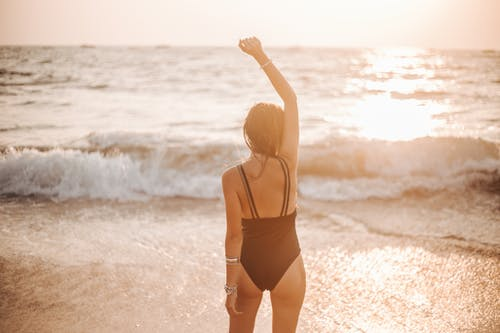 Back View of a Woman Raising Her Hand at The Beach During Sunset