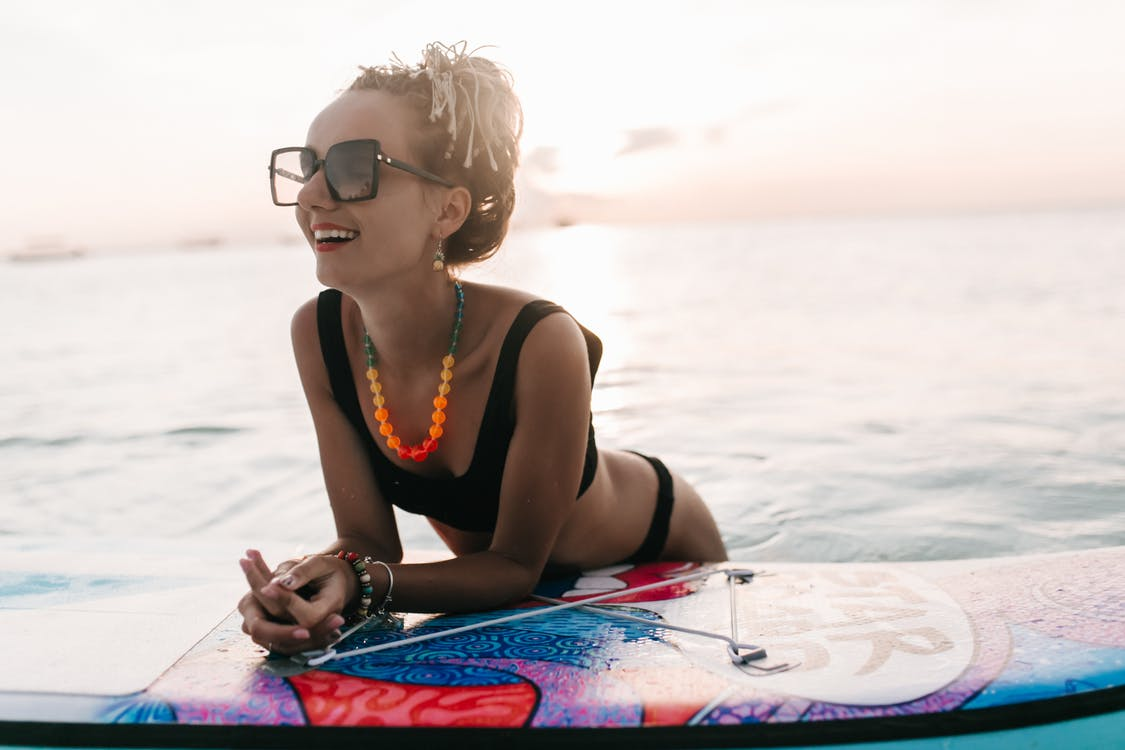 A Woman Leaning Over a Surfboard