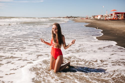 A Woman in a Swimwear Having Fun at the Beach