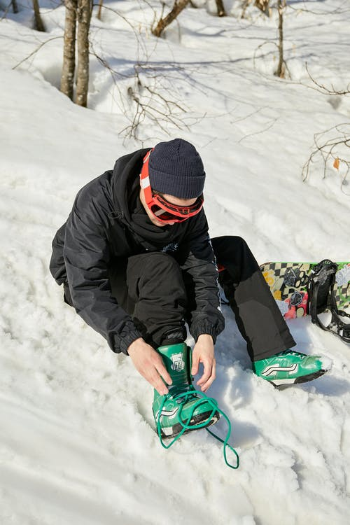 A Snowboarder Tying His Shoes