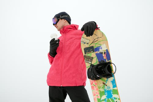 A Man Holding a Snowboard and a Cup of Coffee