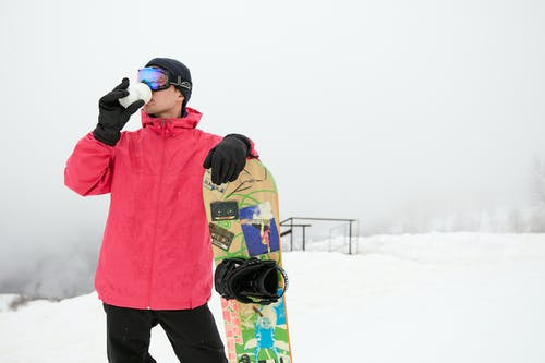 A Man Holding a Snowboard and Drinking Coffee