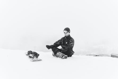 A Man in Winter Clothing Sitting in Lotus Position and Meditating